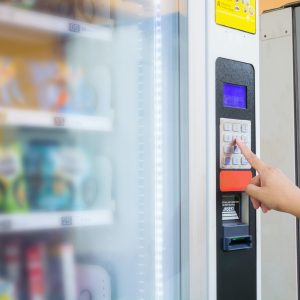 Female Hand Push Button to make Transaction Code or Number on Modern Automatic Vending Machine with Digital Display.  This Machine Can be operated with Both coin and Banknote.